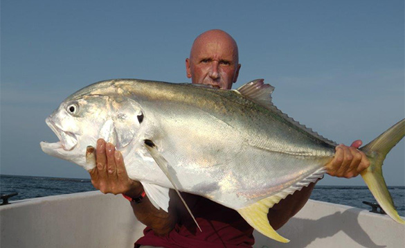 Angler holding a Jack Crevalle fish caught in the Bijagos Archipelago Guinea Bissau/