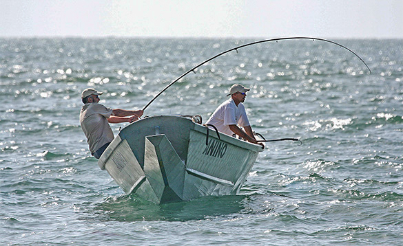 Two anglers fishing from a boat in Guinea Bisau/