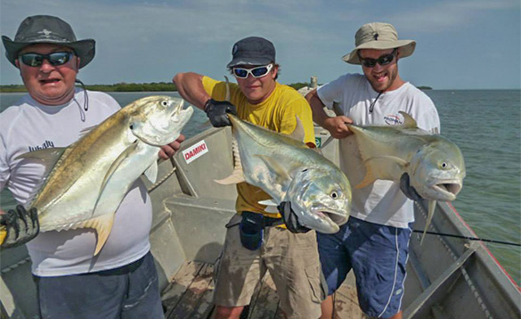 Three anglers each holding a Jack Crevalle fish caught in Guinea Bissau/
