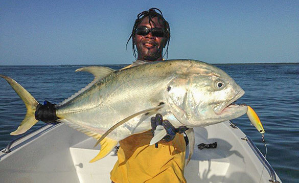 Angler standing on a boat holding a recently caught Jack Crevalle/