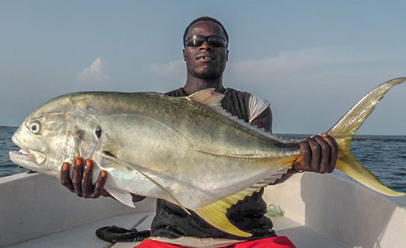 Angler sat on a boat holding a recently caught Jack Crevalle/