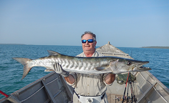 Angler standing on a boat holding a barracuda caught in Guinea Bissau/