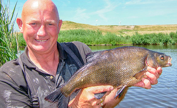 angler holds up a dutch bream/