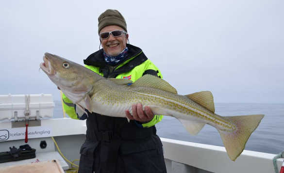 Angler standing on a boat holding a cod caught in Iceland/