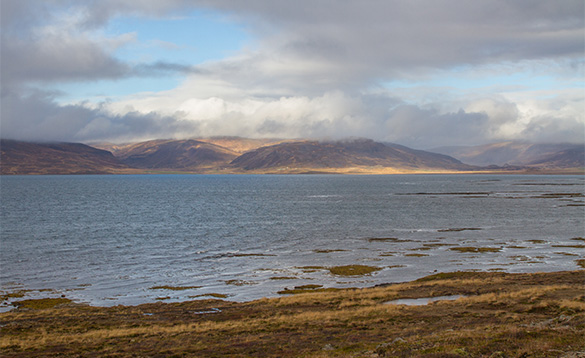 View across water towards hills with low clouds over the top in Iceland/