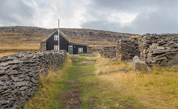 Pathway leading past stone walls to a wooden building in Iceland/