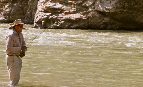 Angler standing in a river in India fishing/