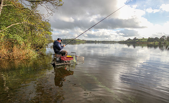 angler fishing on scenic Lough Muckno on a warm sunny day/