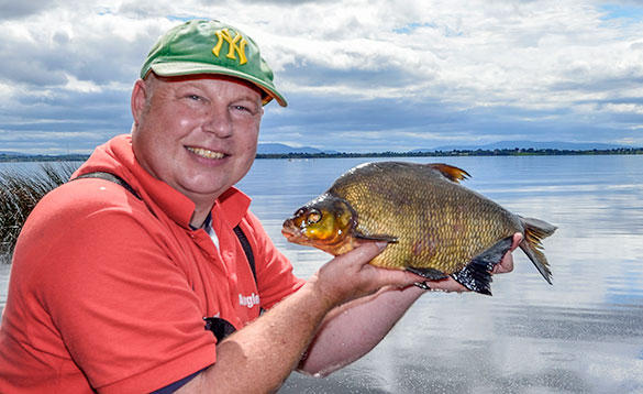 main in a red T shirt and green hat standing in front of a lake holding a bream/