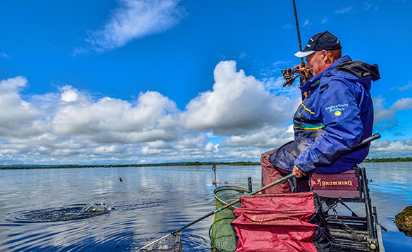 Angler sitting on a tackle box landing a fish caught on Lough Derg/