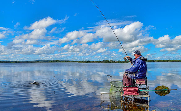 Angler sitting on a tackle box reeling in a fish in the shallow water at the edge of Lough Derg/
