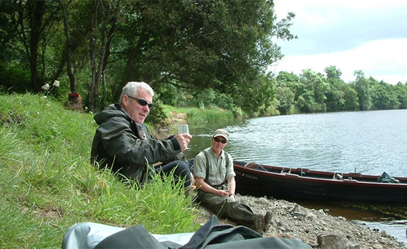 two anglers sitting on a river bank enjoying a drink /