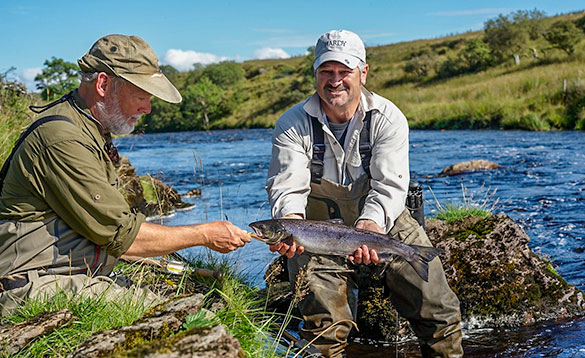 holding small salmon caught on river finn/