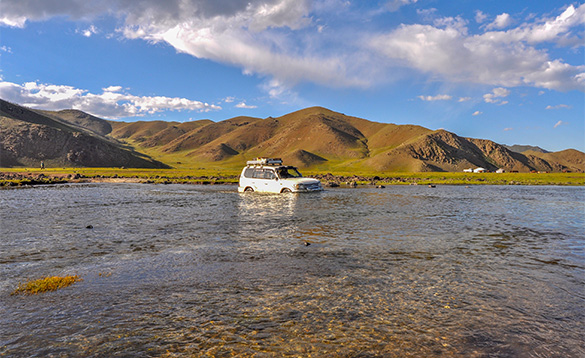 White 4x4 crossing a river in Mongolia/