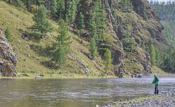 Angler fishing at the edge of a river in Mongolia/