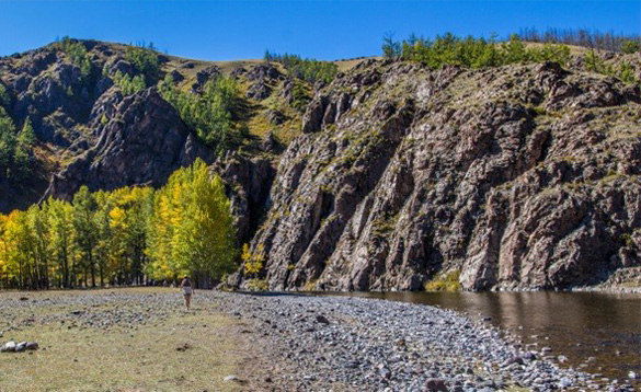 Man walking along a rocky shoreline beside a river in Mongolia/