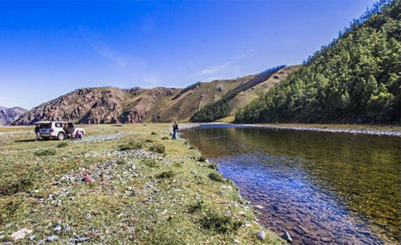 Angler stood beside a crystal clear river fishing in Mongolia /