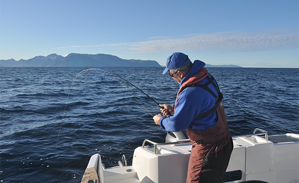 Angler fishing from a boat on a fjord in North Norway/