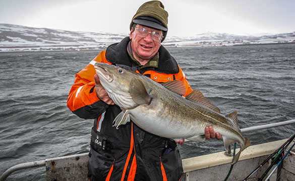 angler standing on a boat in the middle of a fjord holding a cod /