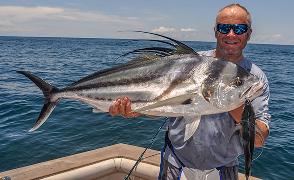 angler with rooster fish caught from boat/