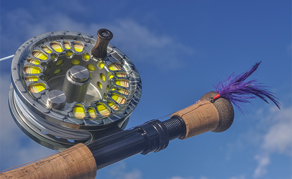 Close up of a fishing rod and reel with a purple fly /