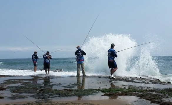 Group of anglers fishing from a rocky shoreline in Mossel Bay/
