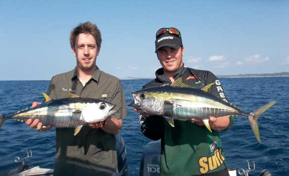 Two anglers standing on a boat each holding bonito fish caught in South Africa/