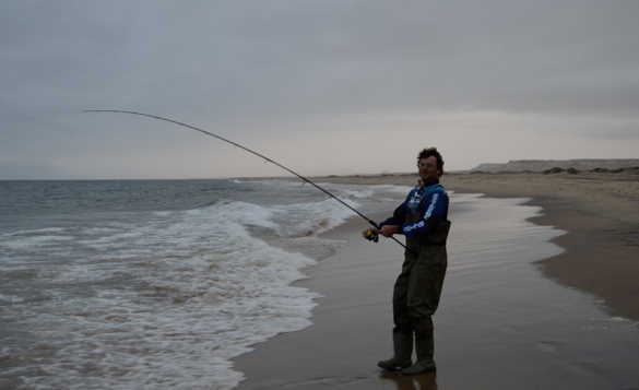 Angler standing at the edge of a sandy beach fishing in the waves/