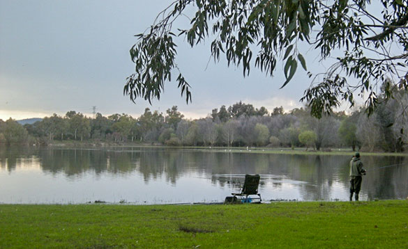 Angler fishing at the edge of a lake in Spain/