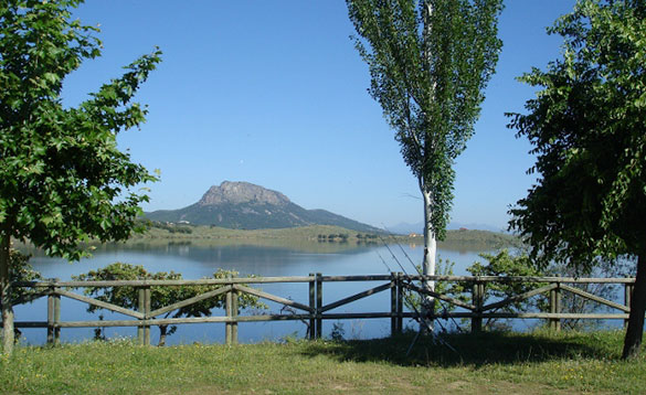 View across a lake in Spain towards grassy hills and craggy mountains/