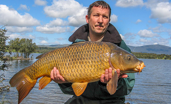 Angler holding a carp beside a lake in Spain/