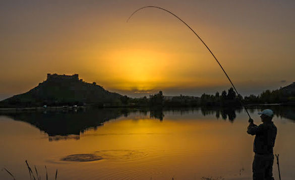 Angler fishing in Spain as the sun rises from behind some hills/