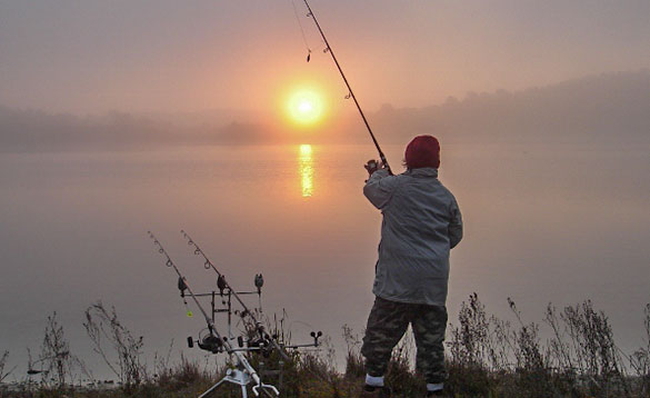 Angler fishing in Spain as the sun rises above the lake/