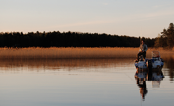 Angler standing on a boat fishing in a scenic lake in Sweden/