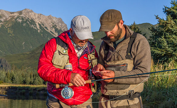 Two anglers holding a fishing rod and discussing the fly used to catch the fish/