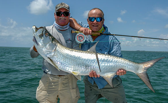 Two anglers holding a large tarpon, bright silver fish/