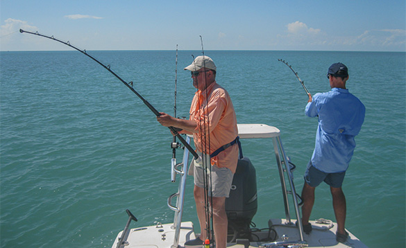 two anglers standing on the rear of a boat fishing/