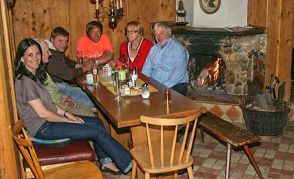 group of adults sitting and chatting around a pine table enjoying a drink/