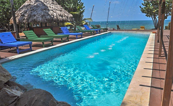 Sunloungers beside a pool at Roberts Grove Beach Resort in Belize/