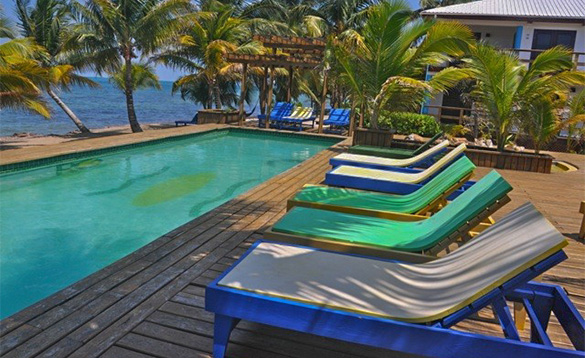 Sun loungers beside a pool at Roberts Grove Beach Resort in Belize/