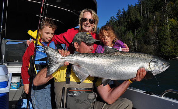 Lady and two children watching a man holding a Coho Salmon that he has caught/