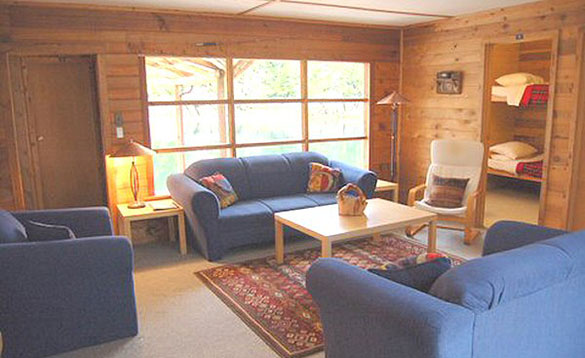 living room of a wooden cabin with blue three piece suite arranged around a light beech coffee table/
