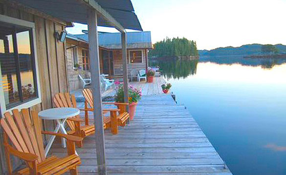 wooden cabins with verandas situated beside a lake/