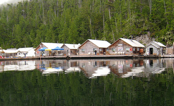 wooden cabins at the foot of tree covered hills beside a lake/