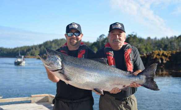 Two anglers standing on a wooden jetty holding a chinook salmon caught in British Columbia/