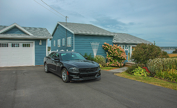 black car parked outside a blue painted wooden bungalow/