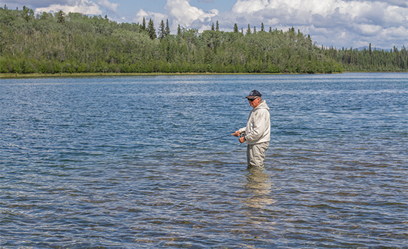 Angler standing in a river fishing in Canada/