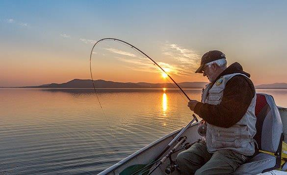 Angler fishing from a boat at sunset/