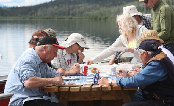 Group of people enjoying lunch beside a lake at Kluane Wilderness Lodge/