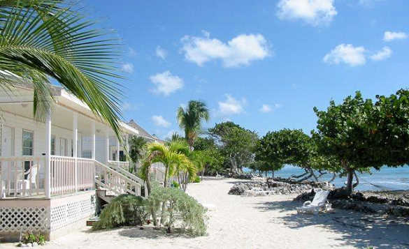 White wooden self-catering villas with verandas and steps leading onto a sandy beach in Little Cayman/